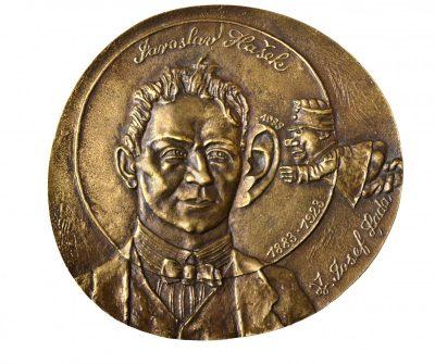 Jaroslavas Hašekas. 1998 m. Bronza, lieta, 11 × 12 cm
